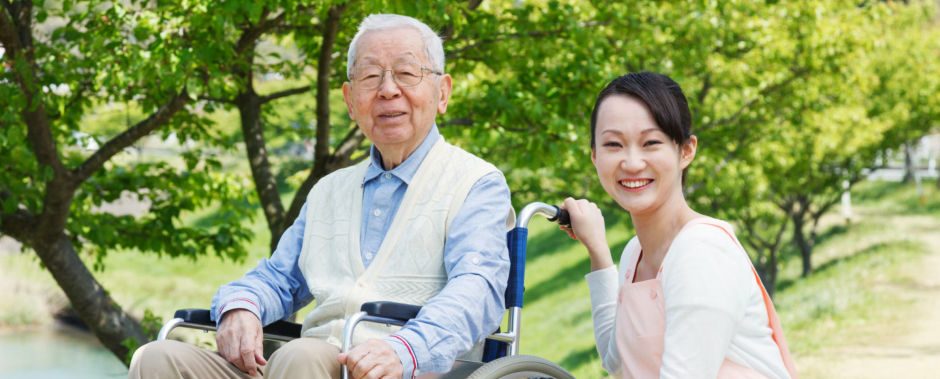 Asian elderly accompanied by his caregiver